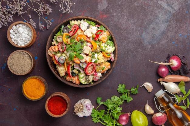Vista dall'alto di verdura fresca. insalata con diversi condimenti su tavola nera