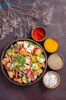 Vista dall'alto di verdura fresca. insalata con diversi condimenti sul nero