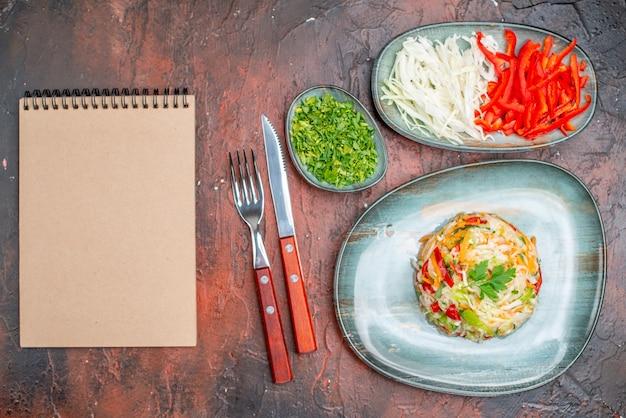 暗いテーブルの上にグリーンスライスキャベツとピーマンとトップビューの新鮮な野菜サラダ