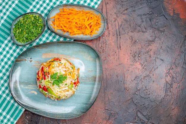 Insalata di verdure fresche vista dall'alto con verdure e carote affettate sul tavolo scuro