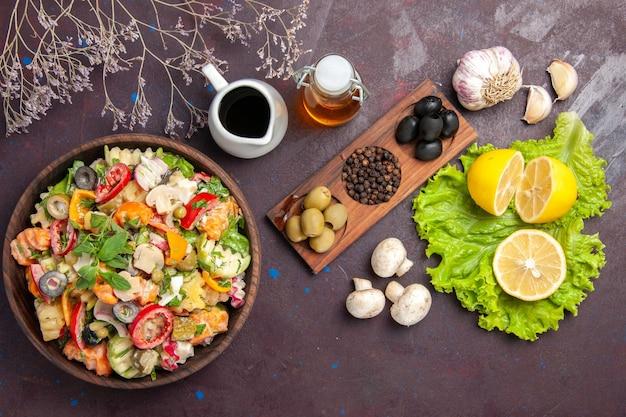 Vista dall'alto di verdura fresca. insalata con fettine di limone su nero