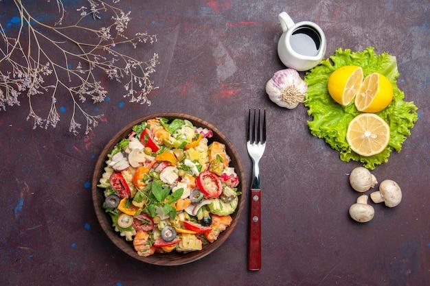 Vista dall'alto di verdura fresca. insalata con fettine di limone e insalata verde su tavola nera