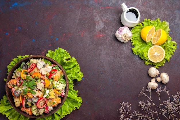 Top view of fresh vegetable. salad with lemon slices and green salad on black