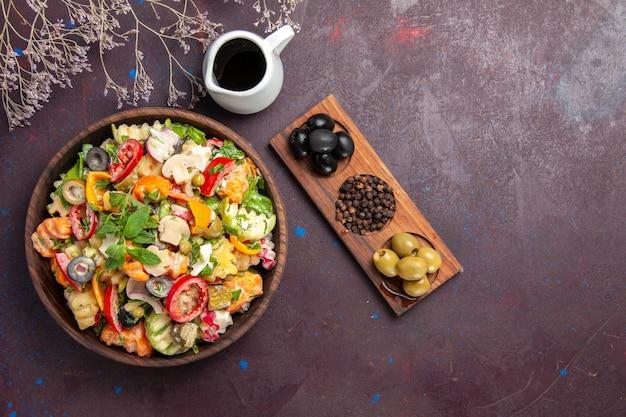 Vista dall'alto di insalata di verdure fresche con olive su nero