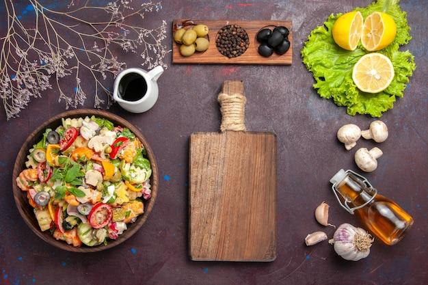 Vista dall'alto di verdura fresca. insalata con olive e fettine di limone su tavola nera