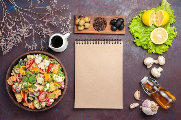 Vista dall'alto di verdura fresca. insalata con olive e fettine di limone su nero