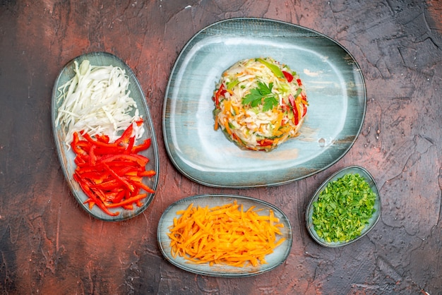 暗いテーブルの上にスライスしたニンジンキャベツとピーマンのトップビュー新鮮な野菜サラダ