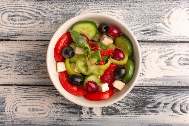 平面図新鮮な野菜サラダスライスしたキュウリトマトオリーブと白チーズの内側のプレートの灰色の机の野菜料理サラダ食事の色