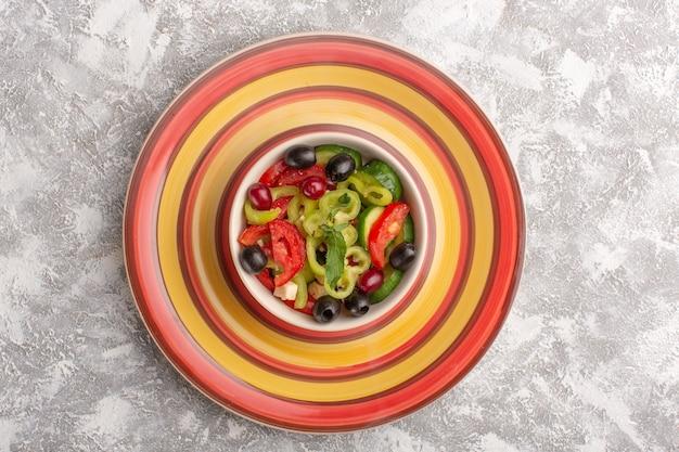 平面図新鮮な野菜のサラダ、スライスしたキュウリ、トマト、オリーブ、白チーズの内側のプレート、灰色のテーブル野菜料理サラダ食事スナック写真