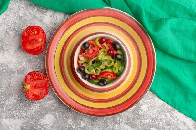 Вид сверху салат из свежих овощей с нарезанными огурцами помидоры оливковое и белый сыр внутри тарелки на сером столе овощная еда салат закуска