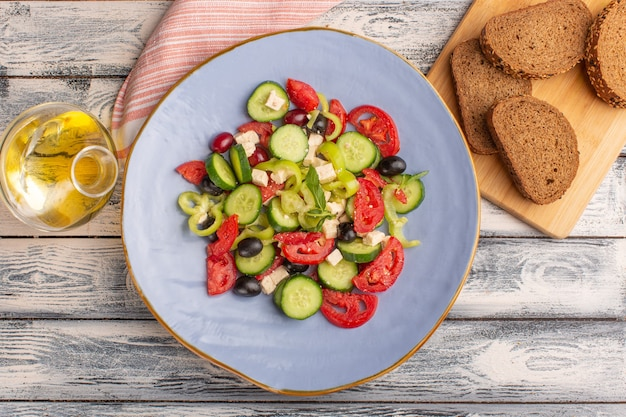 Top view fresh vegetable salad with sliced cucumbers tomatoes olive inside plate with oil and bread on the grey surface vegetable food salad meal color