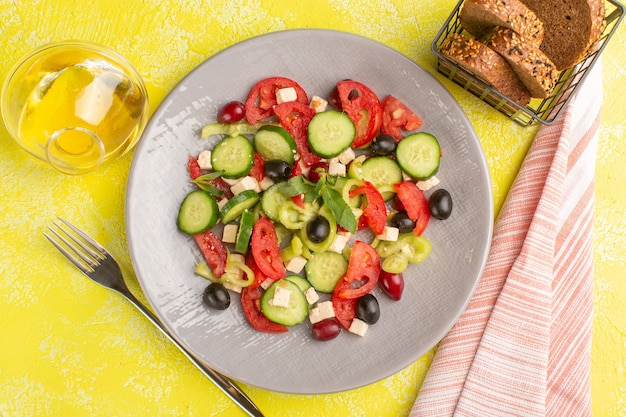 Top view fresh vegetable salad with sliced cucumbers tomatoes olive inside plate with oil and bread on yellow surface vegetable food salad meal color