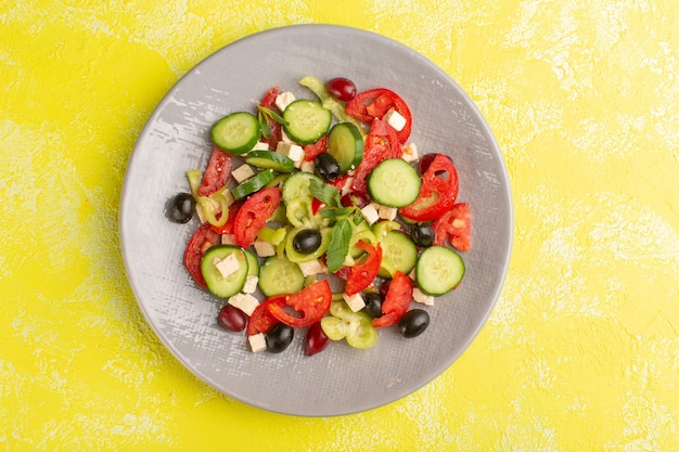 Top view fresh vegetable salad with sliced cucumbers tomatoes olive inside plate on yellow surface vegetable food salad meal color snack