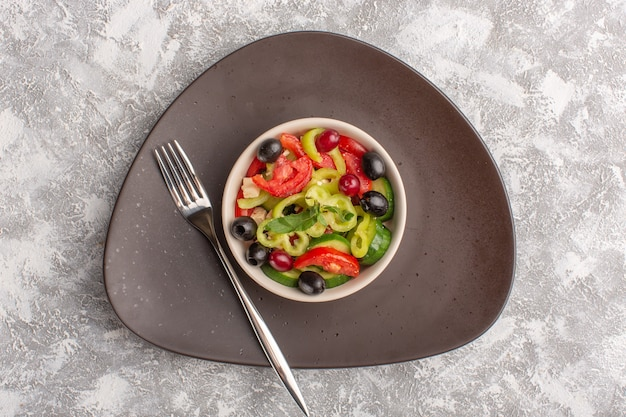 Top view fresh vegetable salad with sliced cucumbers tomatoes olive and white cheese inside brown plate on the grey desk vegetable food salad meal