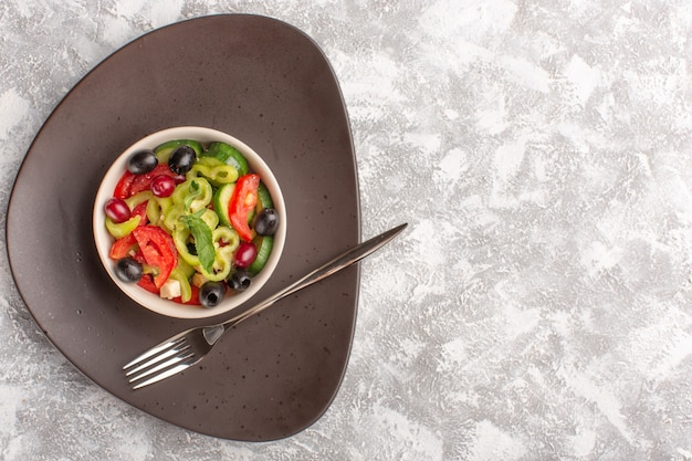 Top view fresh vegetable salad with sliced cucumbers tomatoes olive and white cheese inside brown plate on the grey rustic desk vegetable food salad meal