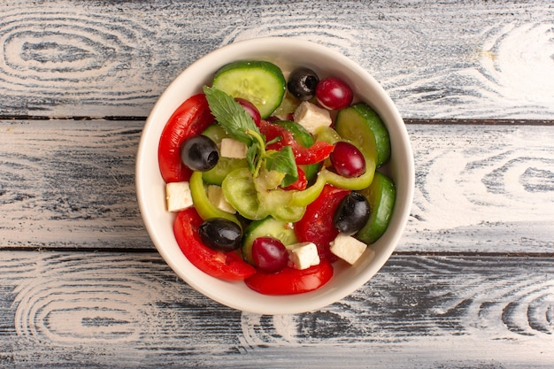 Top view fresh vegetable salad with sliced cucumbers tomatoes olive and white cheese inside plate on the grey desk vegetable food salad meal color