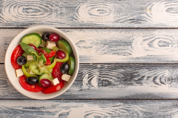 Top view fresh vegetable salad with sliced cucumbers tomatoes olive and white cheese inside plate on the grey desk vegetable salad meal color