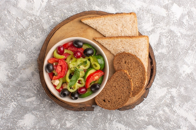 Top view fresh vegetable salad with sliced cucumbers tomatoes olive and white cheese inside plate with sliced bread on the grey desk vegetable food salad meal