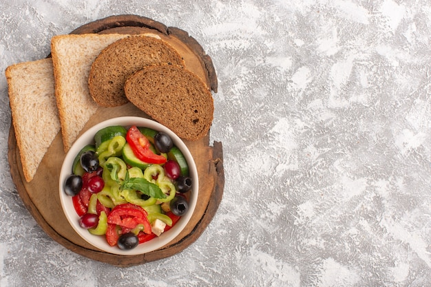Top view fresh vegetable salad with sliced cucumbers tomatoes olive and white cheese inside plate with sliced bread on the grey desk vegetable food salad