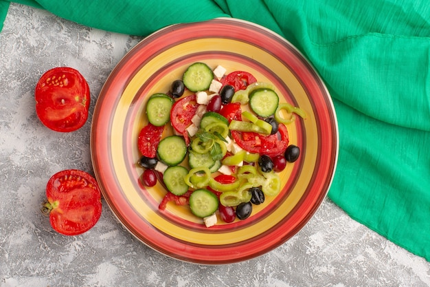 Top view fresh vegetable salad with sliced cucumbers tomatoes olive and white cheese inside plate with tomatoes on the grey surface vegetable food salad meal snack