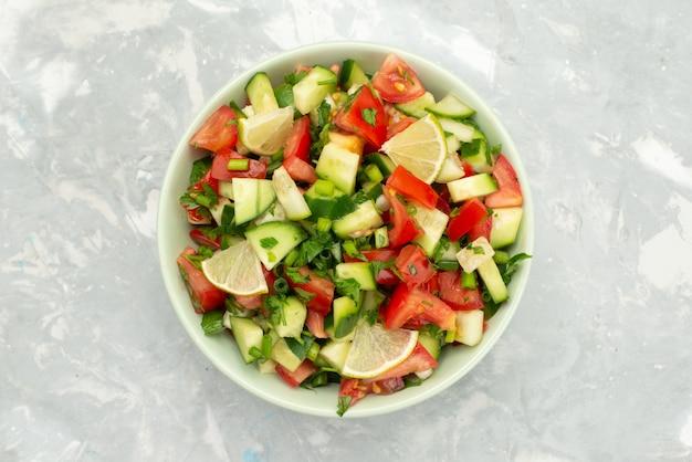 Вид сверху салат из свежих овощей с нарезанными овощами и дольками лимона внутри круглой пластины на синем