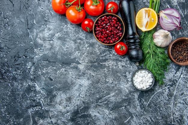 Vista dall'alto ciotole di verdure fresche con semi di melograno sale marino pepe nero cipolla aglio aneto su sfondo grigio spazio copia