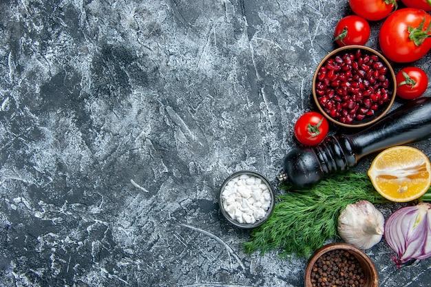 Vista dall'alto ciotole di verdure fresche con semi di melograno sale marino pepe nero cipolla aglio aneto su sfondo grigio spazio libero