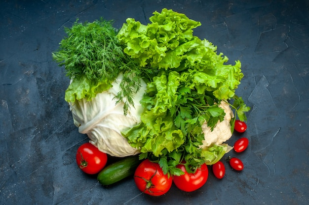 Вид сверху свежие овощи капуста петрушка болгарский перец салат укроп цветная капуста помидоры на темной поверхности