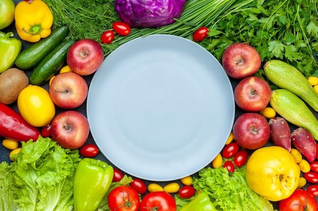 Вид сверху свежие овощи помидоры черри cumcuat редис зеленый лук петрушка огурцы болгарский перец яблоки салат красная капуста круглая тарелка в центре