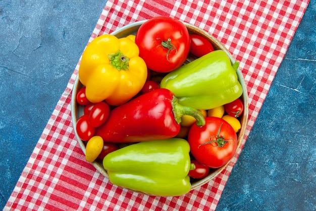 上面図新鮮な野菜チェリートマトさまざまな色ピーマントマトcumcuatボウルに赤と白の市松模様のテーブルクロスに青いテーブル