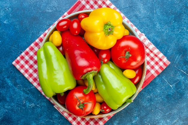 Top view fresh vegetables cherry tomatoes different colors bell peppers tomatoes cumcuat on platter on red white checkered kitchen towel on blue surface