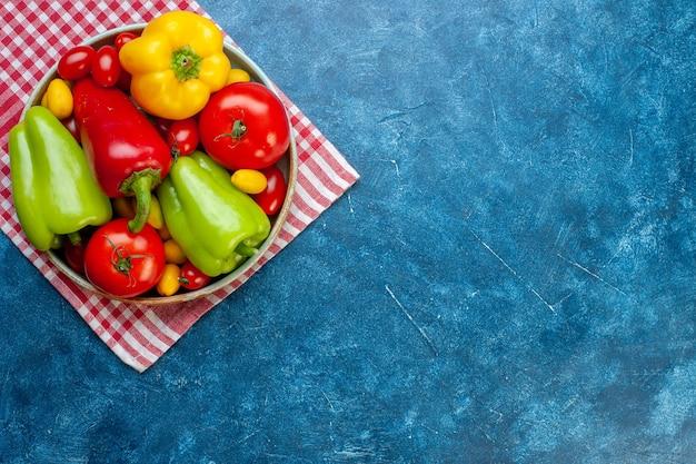 Vista dall'alto verdure fresche pomodorini diversi colori peperoni pomodori cumcuat sul piatto sul tovagliolo da cucina a scacchi bianco rosso sul tavolo blu con lo spazio della copia