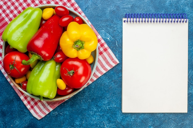 Top view fresh vegetables cherry tomatoes different colors bell peppers tomatoes cumcuat on platter on red and white checkered kitchen towel notebook on blue table