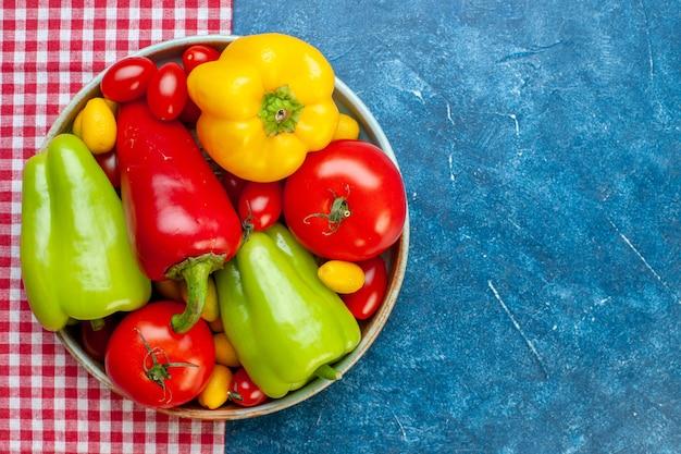 上面図新鮮な野菜チェリートマトさまざまな色ピーマントマトボウルに赤と白の市松模様のテーブルクロス、コピースペース付きの青いテーブル