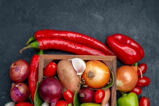 Composizione nella verdura fresca di vista superiore sui colori freschi dell'insalata matura della tavola grigia