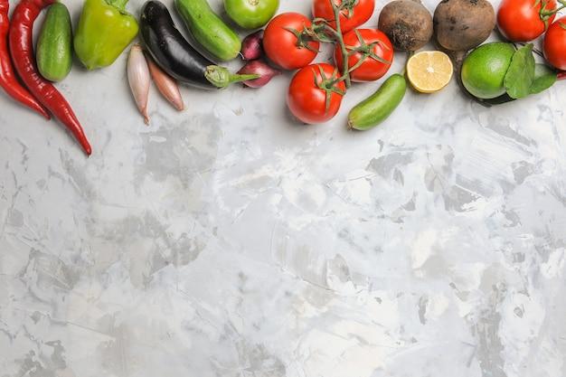 Composizione di verdure fresche vista dall'alto sullo scrittorio bianco