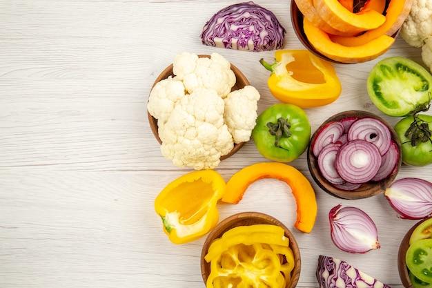 Vista dall'alto verdure fresche tagliate pomodori verdi tagliati cavolo rosso tagliati cipolla tagliata zucca tagliata cavolfiore peperone tagliato in ciotole su superficie di legno bianca spazio libero