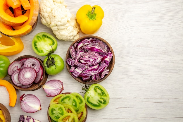 Top view fresh vegetables cut green tomatoes cut red cabbage cut onion cut pumpkin cauliflower cut bell pepper in bowls on white wooden surface with copy space