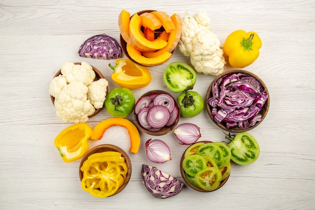 Top view fresh vegetables cut green tomatoes cut red cabbage cut onion cut pumpkin cauliflower cut bell pepper in bowls on white wooden table