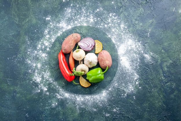Top view fresh vegetables garlic pepper onion and potatoes on dark blue background ripe salad food plant vegetable meal