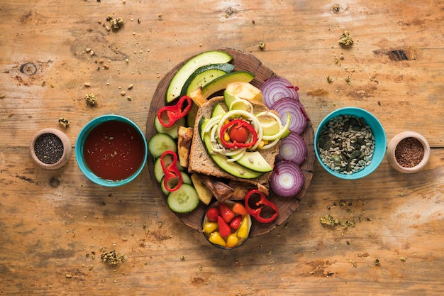 Top view of fresh vegetables and ingredients for sandwich arranged on wooden backdrop