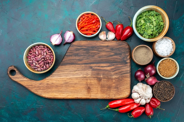 Top view of fresh vegetables onions garlic peppers with greens and beans on dark, food meal ingredient vegetable