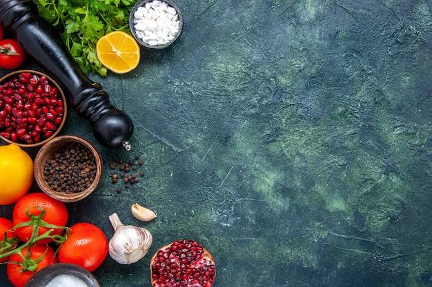 Vista dall'alto verdure fresche macinapepe pomodori aglio verdi melograno sul tavolo con copia posto