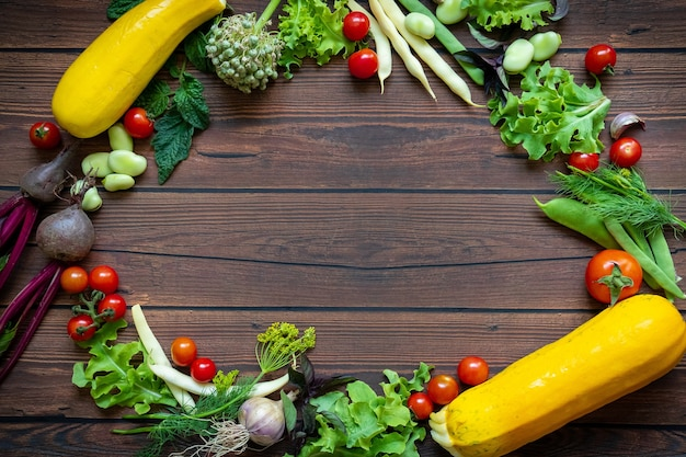 Top view of fresh vegetables placed in a circle on wooden table background with copy space