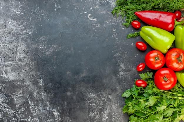 Вид сверху свежие овощи красный и зеленый перец, помидоры черри, укроп, петрушка, помидоры на темной поверхности с местом для копирования