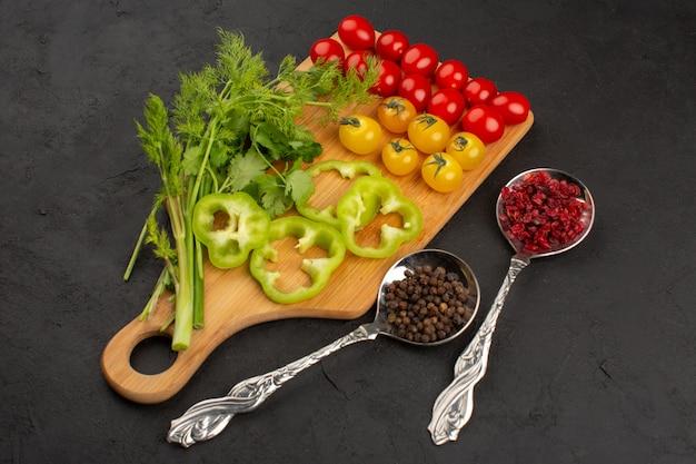 상위 뷰 신선한 야채는 갈색 나무 책상과 회색 바닥에 노란색과 빨간색 토마토와 녹색 등 잘 익은 슬라이스