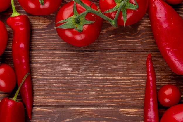 Top view of fresh vegetables ripe tomatoes with red chili peppers on rustic wood with copy space