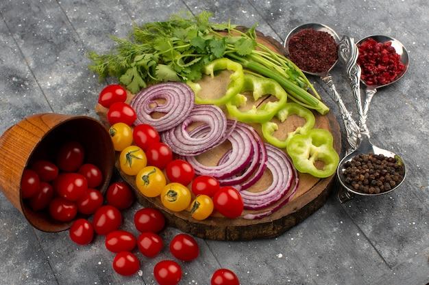 Vista dall'alto verdure fresche affettate e intere come cipolle peperoni verdi pomodori rossi e gialli sulla scrivania marrone e grigio