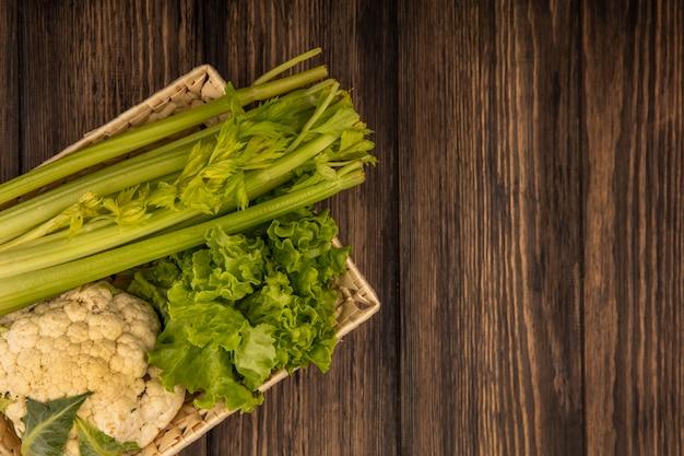 Vista dall'alto di verdure fresche come lattuga sedano e cavolfiore su un secchio su una parete in legno con spazio di copia