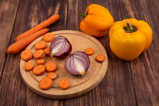 Top view of fresh vegetables such as chopped carrots and red onions on a wooden kitchen board with carrots and yellow bell peppers isolated on a wooden background